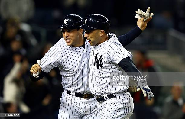 Mark Teixeira and Raul Ibanez of the New York Yankees celebrate after they both scored on a 2run home run hit by Ibanez in the bottom of the ninth...