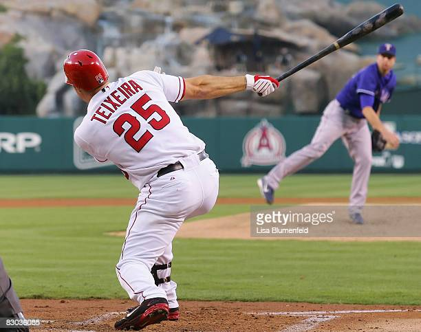 Mark Teixeira of the Los Angeles Angels of Anaheim hits a RBI sacrifice fly in the first inning against the Texas Rangers at Angels Stadium on...