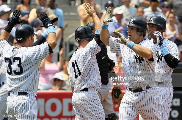 Mark Teixeira of the New York Yankees celebrates his third inning grand slam against the New York Mets with teammates Nick Swisher Brett Gardner and...