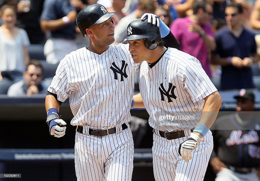 Mark Teixeira #25 (2-R) of the New York Yankees celebrates his third inning grand slam against the New York Mets with teammate Derek Jeter #2 on June 20, 2010 at Yankee Stadium in the Bronx borough of New York City.