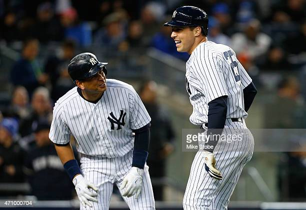 Mark Teixeira of the New York Yankees celebrates with teammate Alex Rodriguez after hitting his second two run home run of the game in the third...