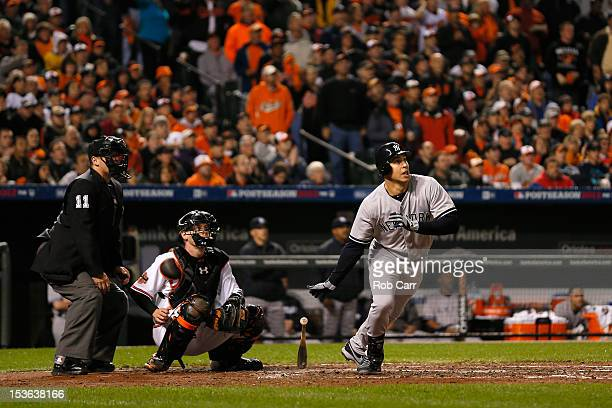 Mark Teixeira of the New York Yankees hits a RBI single in the top of the fourth inning against the Baltimore Orioles during Game One of the American...