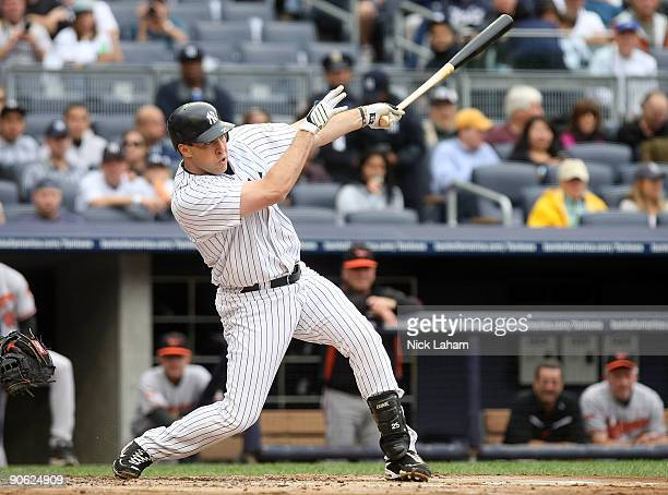 Mark Teixeira of the New York Yankees hits a sacrifice fly to score the run of Derek Jeter in the first inning against the Baltimore Orioles on...