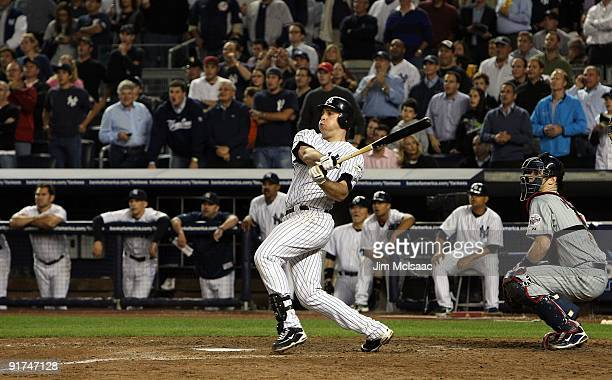 Mark Teixeira of the New York Yankees hits a walk off home run in the eleventh inning as Joe Mauer of the Minnesota Twins looks on in Game Two of the...