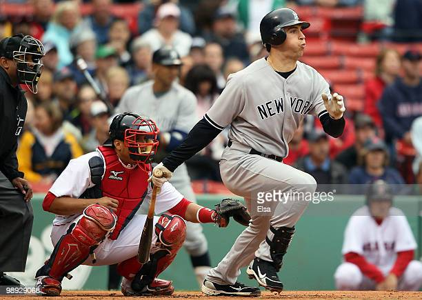 Mark Teixeira of the New York Yankees hits an RBI single in the first inning as Victor Martinez of the Boston Red Sox defends on May 8, 2010 at...