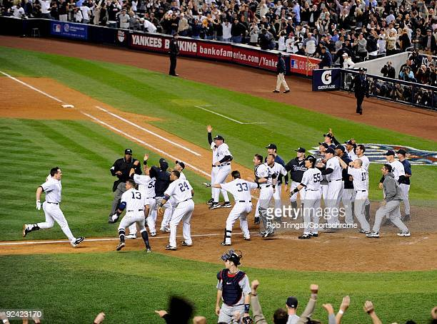 Mark Teixeira of the New York Yankees is greeted by his teammates at home plate after hitting a walk off home run in the eleventh inning against the...