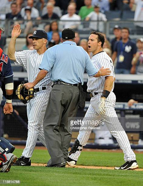 Mark Teixeira of the New York Yankees is restrained by Joe Girardi of the New York Yankees and home plate umpire Dale Scott after being hit by a...