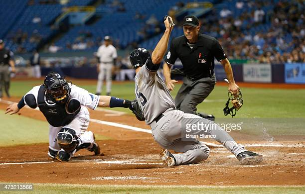 Mark Teixeira of the New York Yankees is tagged out at home by catcher Bobby Wilson of the Tampa Bay Rays to end the top of the fifth inning of a...