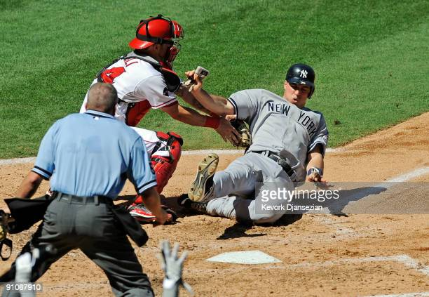 Mark Teixeira of the New York Yankees is tagged out at home plate by catcher Mike Napoli of the Los Angeles Angels of Anaheim on a throw from left...