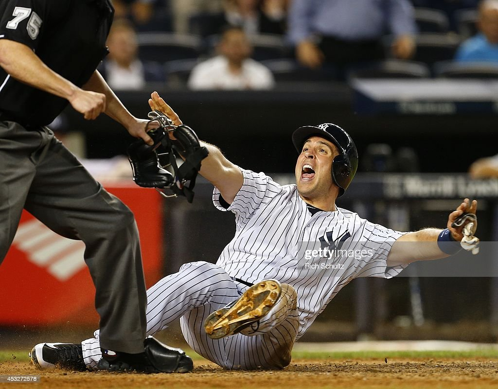 Mark Teixeira #25 of the New York Yankees reacts after being called out by home plate umpire Tom Woodring #75 the play was reversed on video review as the tag by catcher Bryan Holaday #50 of the Detroit Tigers was late during the eighth inning of a MLB baseball game at Yankee Stadium on August 6, 2014 in the Bronx borough of New York City. The Yankees defeated the Tigers 5-1.