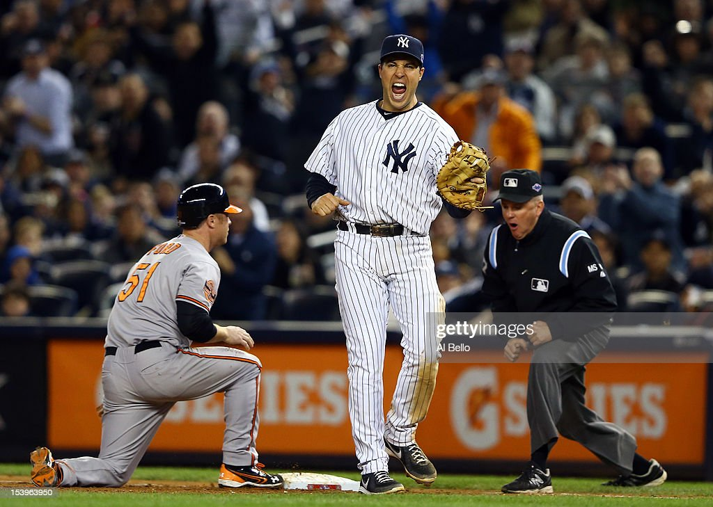 Mark Teixeira #25 of the New York Yankees reacts after Lew Ford #51 of the Baltimore Orioles was picked off at first base during Game Four of the American League Division Series at Yankee Stadium on October 11, 2012 in the Bronx borough of New York City.