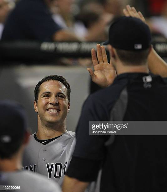 Mark Teixiera of the New York Yankees smiles as he is greeted by teammates in the dugout after hitting a runscoring triple and then scoring in the...