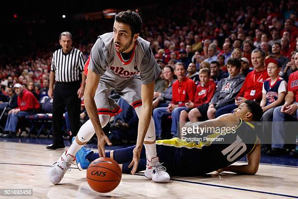 Mark Tollefsen of the Arizona Wildcats controls the ball ahead of Jaleni Neely of the Northern Arizona Lumberjacks during the first half of the...