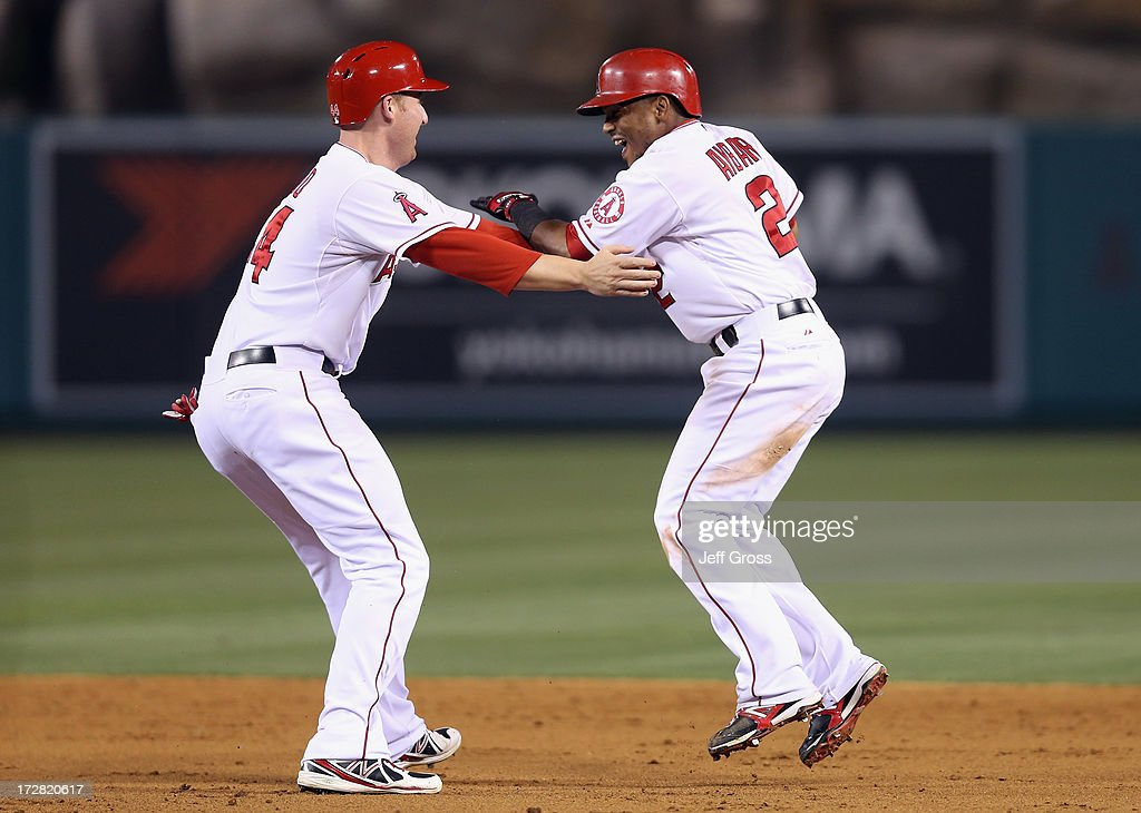 Mark Trumbo (L) #44 and Erick Aybar #2 of the Los Angeles Angels of Anaheim celebrate Aybar's walk off single against the St. Louis Cardinals in the ninth inning at Angel Stadium of Anaheim on July 4, 2013 in Anaheim, California. The Angels defeated the Cardinals 6-5.