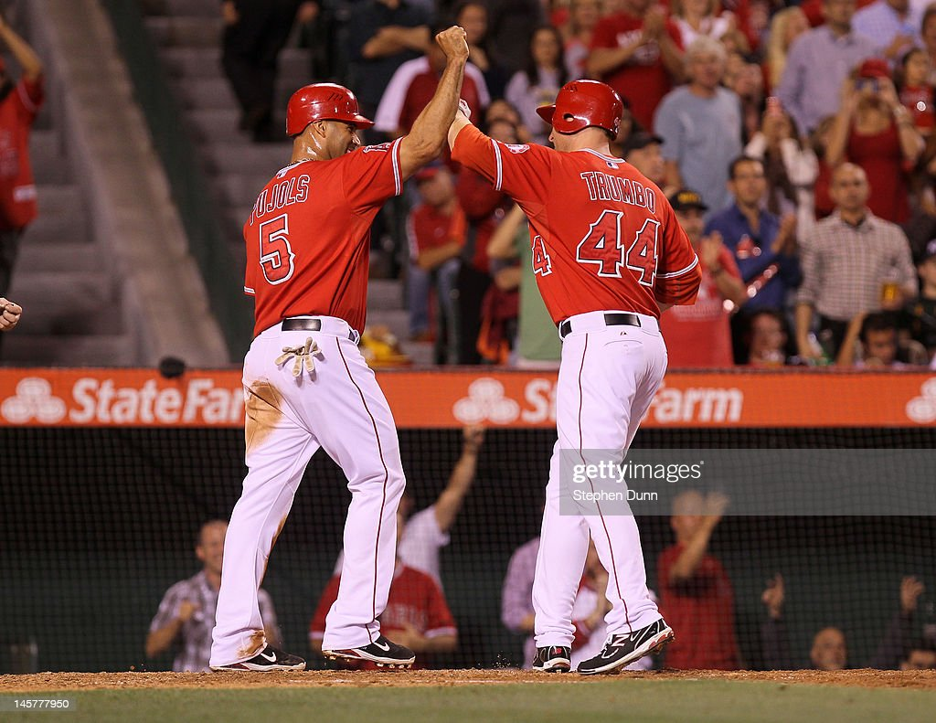 Mark Trumbo #44 and Albert Pujols #5 of the Los Angeles Angels of Anaheim celebrate as the both score on Trumbo's two run home run in the fifth inning against the Seattle Mariners at Angel Stadium of Anaheim on June 5, 2012 in Anaheim, California.
