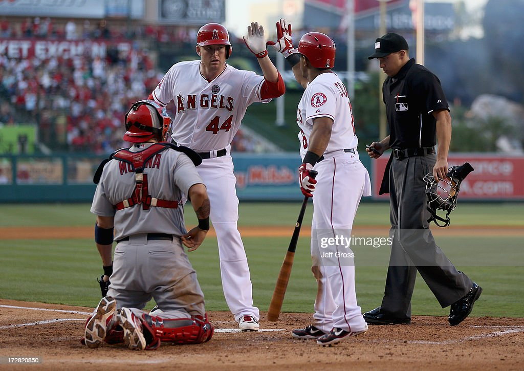 Mark Trumbo #44 and Alberto Callaspo #6 of the Los Angeles Angels of Anaheim celebrate Trumbo's solo home run, as catcher Yadier Molina #4 of the St. Louis Cardinals the St. Louis Cardinals and umpire Adam Hamari look on in the fourth inning at Angel Stadium of Anaheim on July 4, 2013 in Anaheim, California. The Angels defeated the Cardinals 6-5.