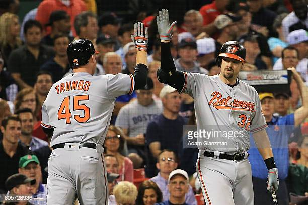 Mark Trumbo high fives Matt Wieters of the Baltimore Orioles after hitting a solo home run in the second inning of a game against the Boston Red Sox...