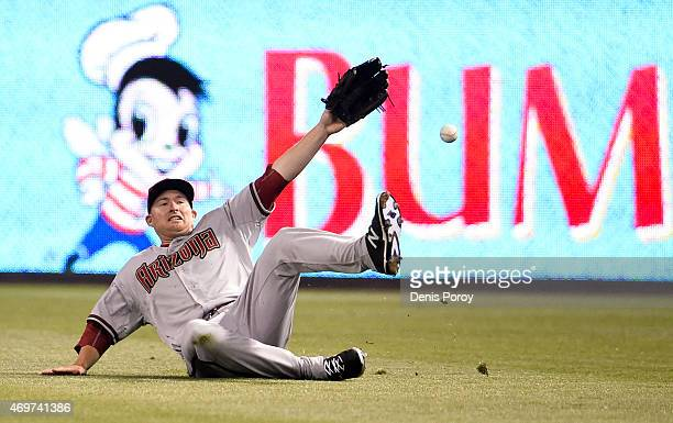 Mark Trumbo of the Arizona Diamondbacks can't make the catch on a triple hit by Matt Kemp of the San Diego Padres during the seventh inning of a...
