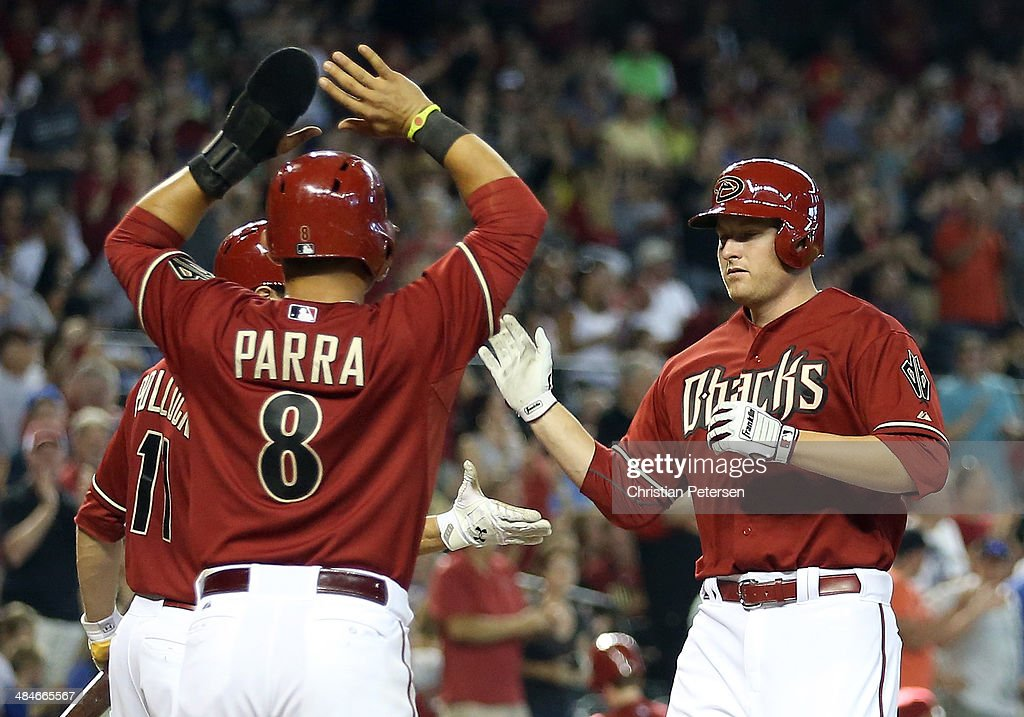 Mark Trumbo #15 of the Arizona Diamondbacks high-fives A.J. Pollock #11 and Gerardo Parra #8 after Trumbo hit a three-run home run against the Los Angeles Dodgers during the seventh inning of the MLB game at Chase Field on April 13, 2014 in Phoenix, Arizona. The Dodgers defeated the Diamondbacks 8-6.