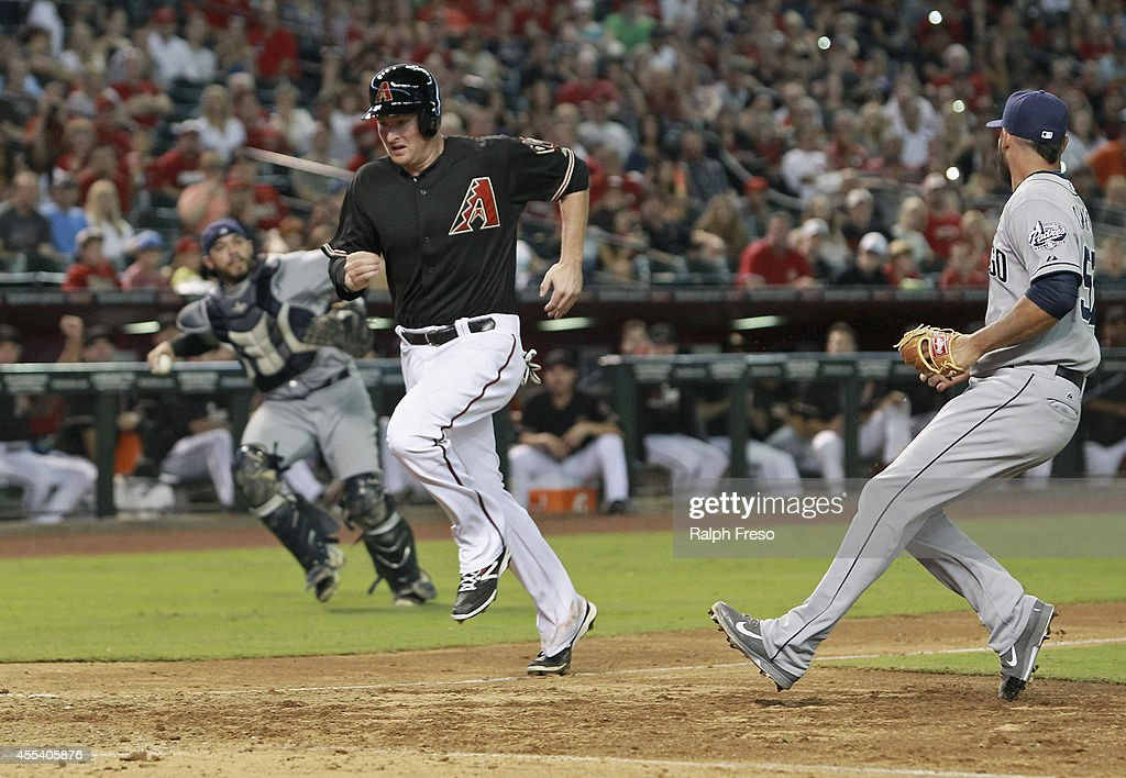 Mark Trumbo #15 of the Arizona Diamondbacks scores on a pass ball as pitcher Leonel Campos #57 of the San Diego Padres (R) tries to cover home on the throw from catcher Rene Rivera #44 during the seventh inning of a MLB game at Chase Field on September 13, 2014 in Phoenix, Arizona.
