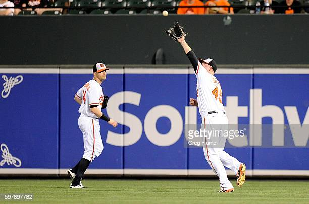 Mark Trumbo of the Baltimore Orioles catches a fly ball in the seventh inning hit by Devon Travis of the Toronto Blue Jays at Oriole Park at Camden...