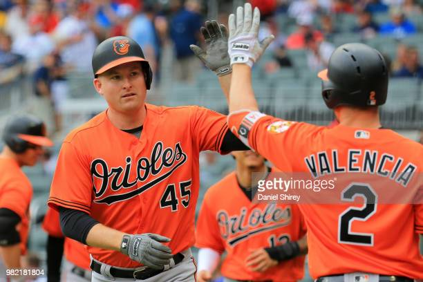 Mark Trumbo of the Baltimore Orioles celebrates a grand slam with Danny Valencia during the first inning against the Atlanta Braves at SunTrust Park...
