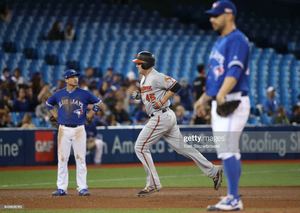 Mark Trumbo #45 of the Baltimore Orioles circles the bases after hitting a solo home run in the fifth inning during MLB game action as Marco Estrada #25 of the Toronto Blue Jays reacts at Rogers Centre on September 11, 2017 in Toronto, Canada.
