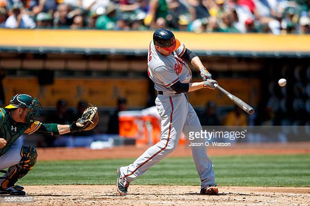 Mark Trumbo of the Baltimore Orioles hits an RBI single against the Oakland Athletics during the fourth inning at the Oakland Coliseum on August 11...