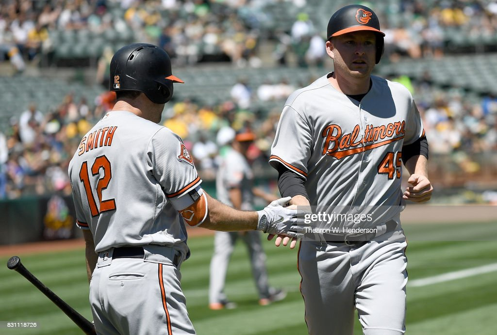 Mark Trumbo #45 of the Baltimore Orioles is congratulated by Seth Smith #12 after Trumbo scored against the Oakland Athletics in the top of the second inning at Oakland Alameda Coliseum on August 13, 2017 in Oakland, California.