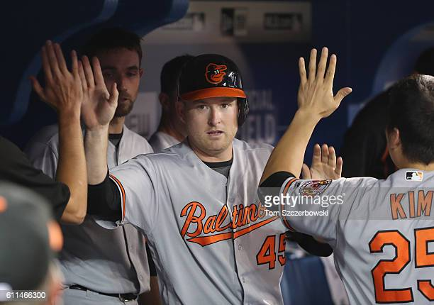 Mark Trumbo of the Baltimore Orioles is congratulated by teammates in the dugout after scoring a run in the eighth inning during MLB game action...