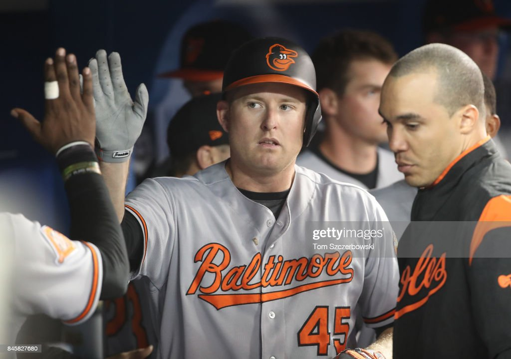 Mark Trumbo #45 of the Baltimore Orioles is congratulated by teammates in the dugout after hitting a solo home run in the fifth inning during MLB game action as Marco Estrada #25 of the Toronto Blue Jays reacts at Rogers Centre on September 11, 2017 in Toronto, Canada.