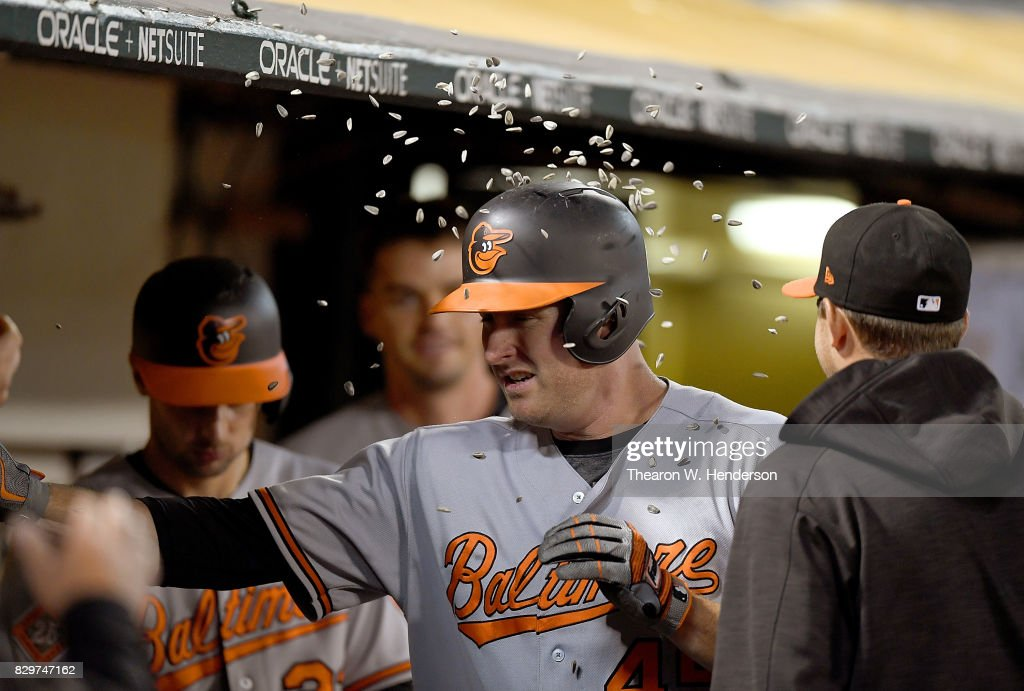 Mark Trumbo #45 of the Baltimore Orioles is congratulated by teammates and showered with sunflower seeds after hitting a solo home run against the Oakland Athletics in the top of the six inning at Oakland Alameda Coliseum on August 10, 2017 in Oakland, California. The Orioles won the game 7-2.