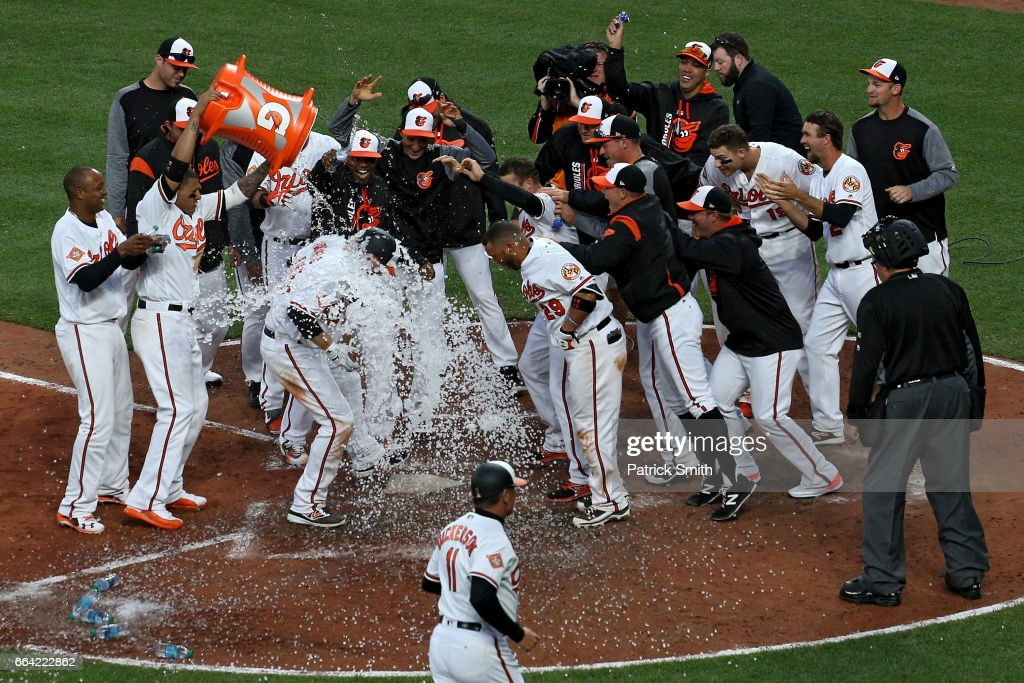 Mark Trumbo #45 of the Baltimore Orioles is greeted at home plate after hitting a walk-off home run against the Toronto Blue Jays during the eleventh inning in their Opening Day game at Oriole Park at Camden Yards on April 3, 2017 in Baltimore, Maryland. The Baltimore Orioles won, 3-2, in the eleventh inning.