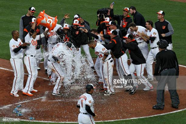 Mark Trumbo of the Baltimore Orioles is greeted at home plate after hitting a walkoff home run against the Toronto Blue Jays during the eleventh...