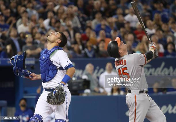 Mark Trumbo of the Baltimore Orioles looks up as he pops out in foul territory in the fifth inning during MLB game action as Luke Maile of the...