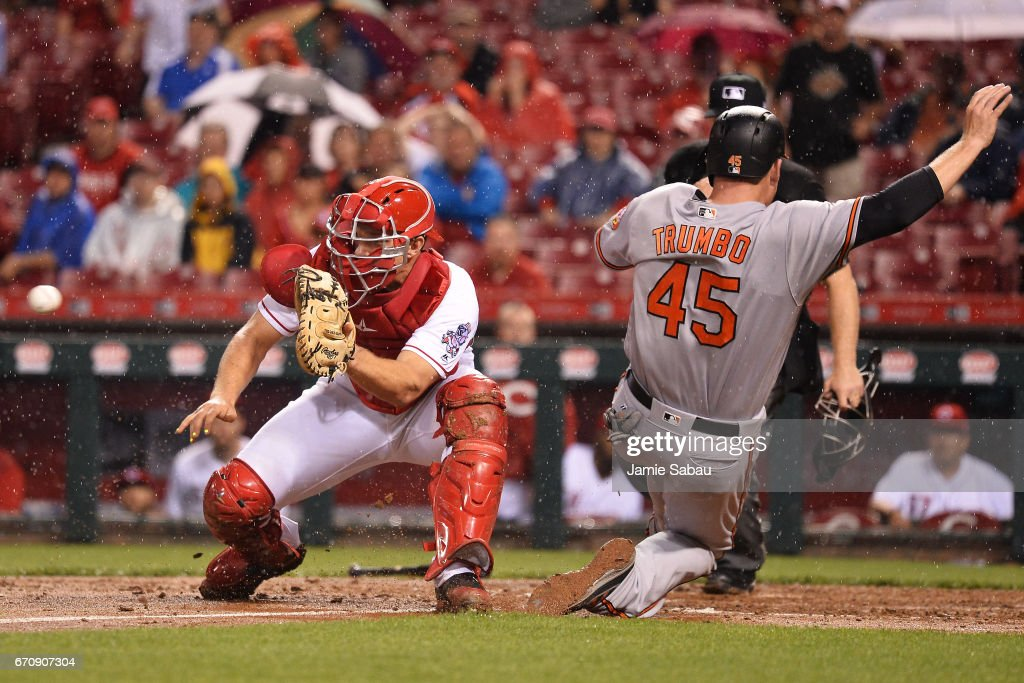 Mark Trumbo #45 of the Baltimore Orioles slides home for the game-winning run in the 10th inning as catcher Stuart Turner #32 of the Cincinnati Reds takes the throw at Great American Ball Park on April 20, 2017 in Cincinnati, Ohio. Baltimore defeated Cincinnati 2-1.