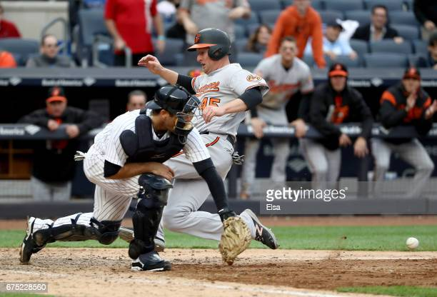 Mark Trumbo of the Baltimore Orioles slides home safely in the 11th inning as Austin Romine of the New York Yankees defends on April 30 2017 at...