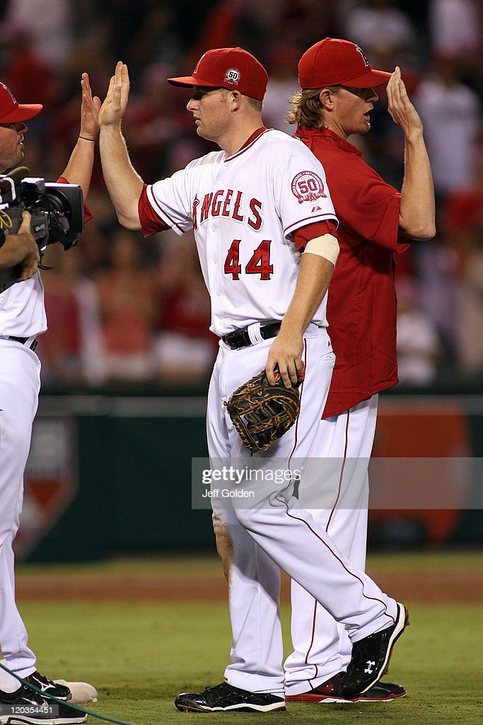 Mark Trumbo #44 of the Los Angeles Angels of Anaheim high-fives teammates after the victory against the Minnesota Twins at Angel Stadium on August 04, 2011 in Anaheim, California. The Angels won 7-1.