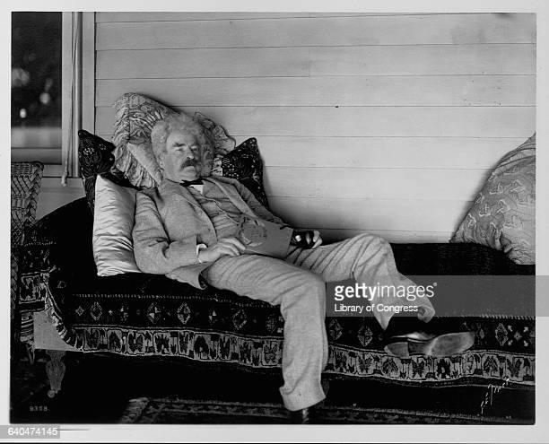 Mark Twain reclines on a sofa with a book