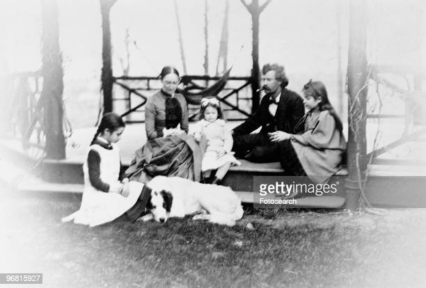 Mark Twain with family seated outside circa 1865