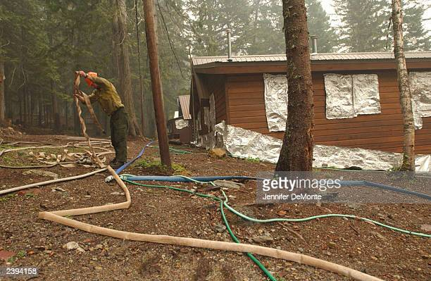 Mark Urbani a Mendocino hotshot crew member from Fort Bragg Califfornia sets up sprinklers to help protect structures August 12 2003 in Glacier...