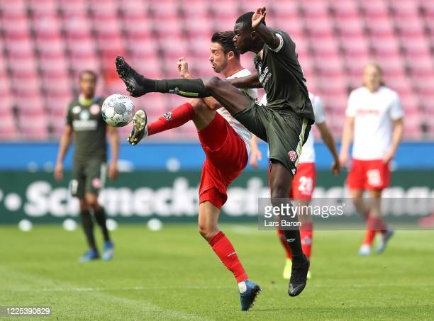 Mark Uth of 1 FC Koeln is challenged by Moussa Niakhate of FSV Mainz 05 during the Bundesliga match between 1 FC Koeln and 1 FSV Mainz 05 at...