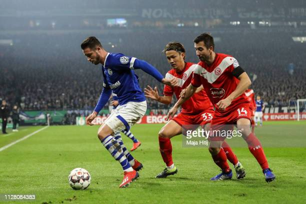 Mark Uth of FC Schalke 04 battle for possession with Takashi Usami of Fortuna Duesseldorf and Markus Suttner of Fortuna Duesseldorf during the DFB...