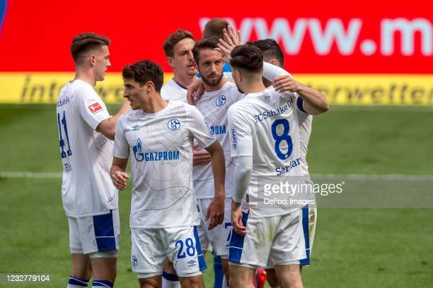 Mark Uth of FC Schalke 04 celebrates after scoring his team's first goal with teammates during the Bundesliga match between TSG Hoffenheim and FC...