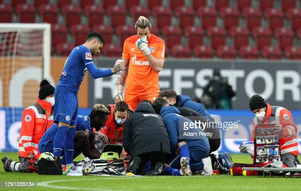 Mark Uth of FC Schalke 04 is checked on by teammates as he receives treatment after a challenge during the Bundesliga match between FC Augsburg and...