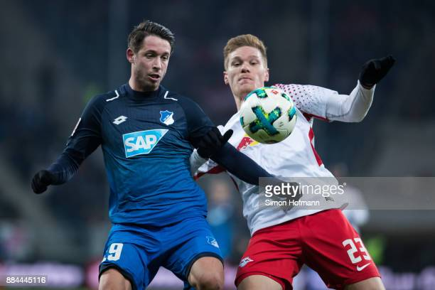 Mark Uth of Hoffenheim is challenged by Marcel Halstenberg of Leipzig during the Bundesliga match between TSG 1899 Hoffenheim and RB Leipzig at...