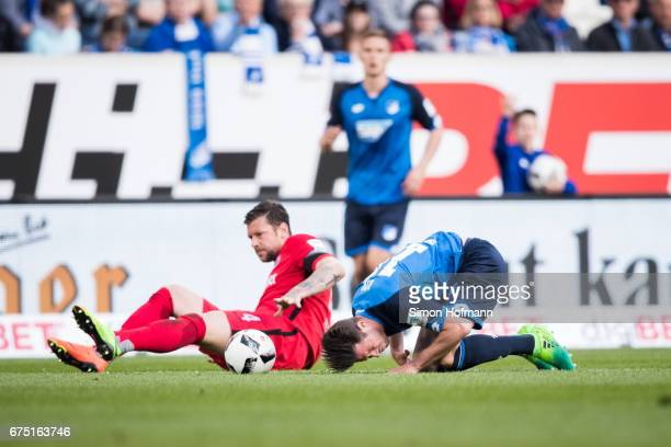 Mark Uth of Hoffenheim is tackled by Marco Russ of Frankfurt during the Bundesliga match between TSG 1899 Hoffenheim and Eintracht Frankfurt at...