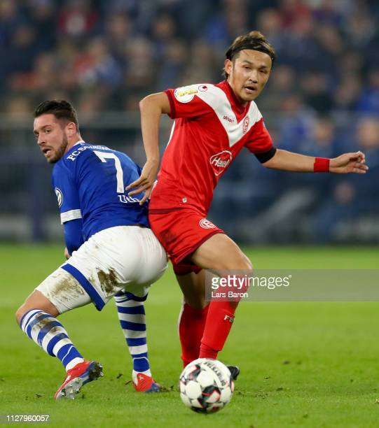 Mark Uth of Schalke challenges Takashi Usami of Duesseldorf during the DFB Pokal Cup match between FC Schalke 04 and Fortuna Duesseldorf at...