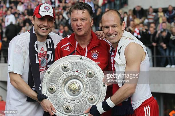 Mark van Bommel, head coach Louis van Gaal and Arjen Robben of Bayern present the German Championship trophy during the Bundesliga match between...