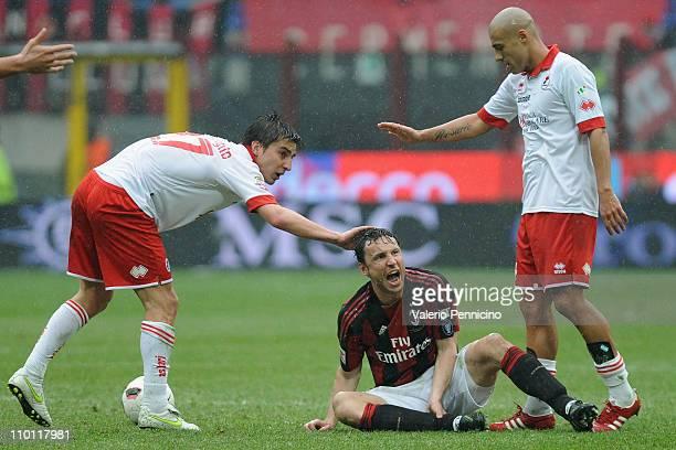 Mark van Bommel of AC Milan reacts against Simone Bentivoglio and Sergio Bernardo Almiron of AS Bari during the Serie A match between AC Milan and AS...
